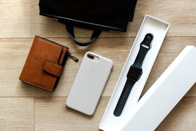 Умные часы, бумажник и мобильный телефон на деревянном столе.
