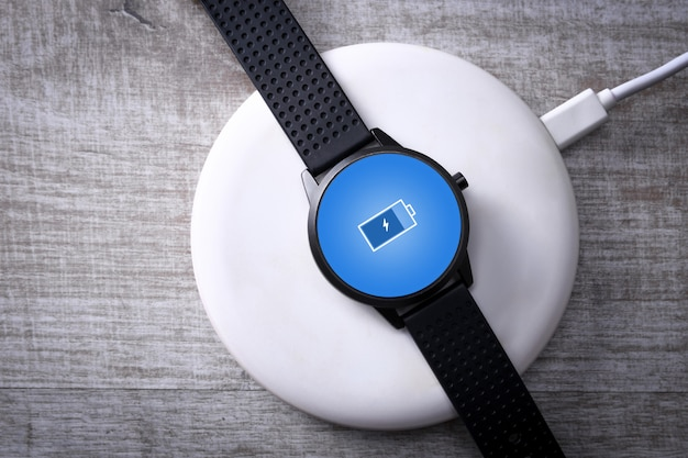 Smart watch on wireless charging with on-screen charging indicator. at the desktop, near the laptop. top view. place for text