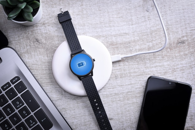 Smart watch on wireless charging with on-screen charging indicator. at the desktop, near the laptop. top view.