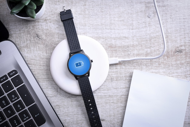 Smart watch on wireless charging with on-screen charging indicator.