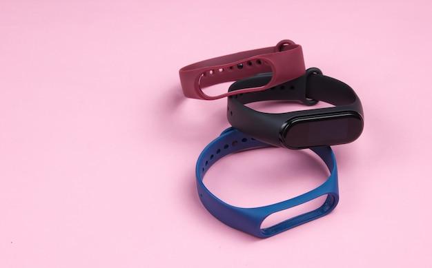 ピンクの背景に交換可能なブレスレットを備えたスマートウォッチ。フィットネストラッカー。現代のガジェット