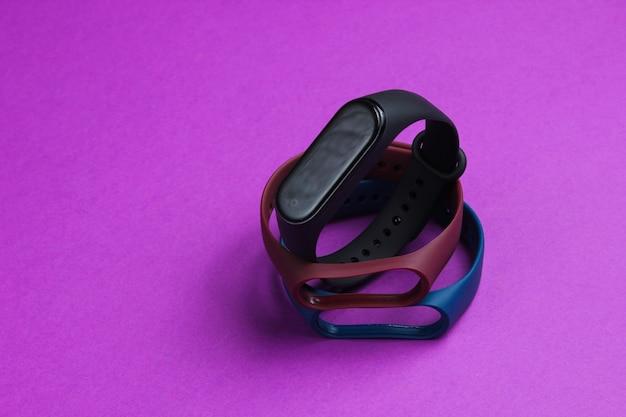 紫色の背景に交換可能なブレスレットを備えたスマートウォッチ。フィットネストラッカー。現代のガジェット