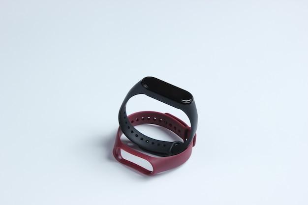 Умные часы со сменными браслетами на белом фоне. фитнес-трекер. современные гаджеты