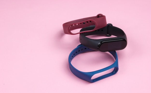 Smart watch with interchangeable bracelets on pink background. fitness tracker. modern gadgets