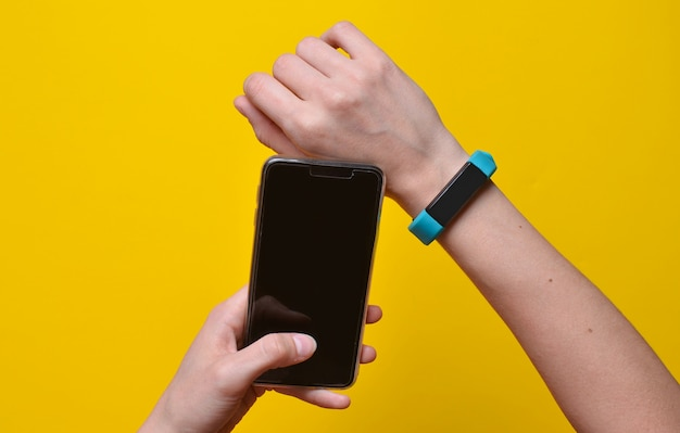 Smart watch on the wrist and a smartphone in the hand synchronization.