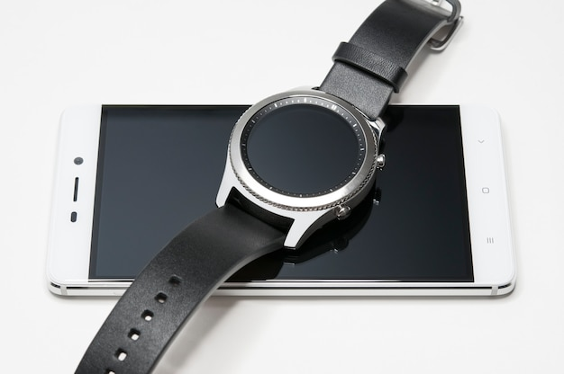 Smart watches are on the smartphone, isolated on a white background.