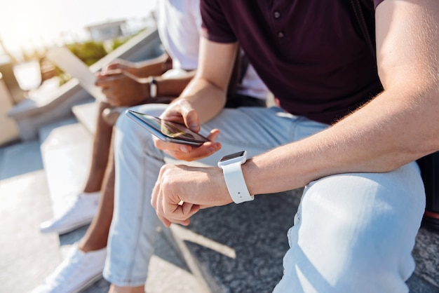 Smart watches. handsome man putting left arm on his knee and checking time while sitting on the foreground