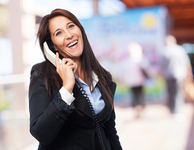 Smart woman laughing while talking on the phone