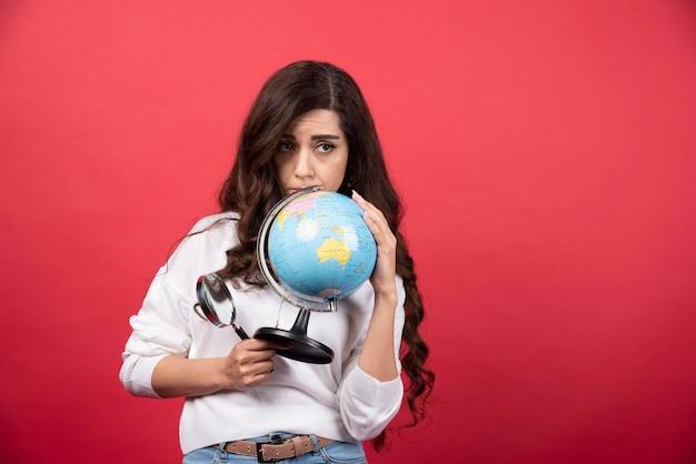 Donna intelligente in posa con globo e lente d'ingrandimento. foto di alta qualità
