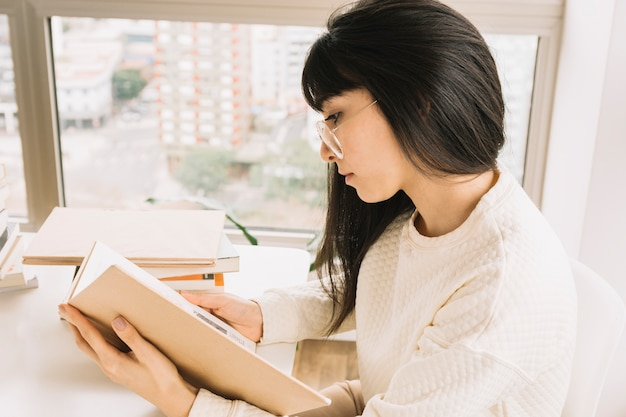Умная женщина, читающая за столом
