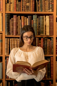 Smart woman reading book in library