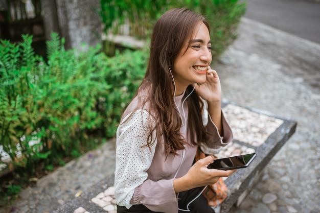 Умная женщина сидит на скамейке в парке, слушает музыку