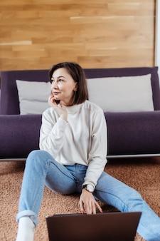 Умная женщина работает на ноутбуке, сидя на полу дома в дневное время одет