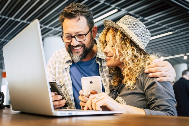 Умный рабочий и цифровой кочевник. альтернативная концепция офиса eveywhere с парой кавказских людей, использующих телефоны, устройства и портативный компьютер