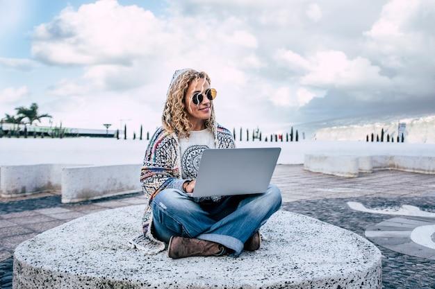 彼女の足にコンピューターのラップトップで屋外で働く陽気な幸せで無料の白人女性とスマートな作業とデジタル遊牧民のライフスタイルの概念
