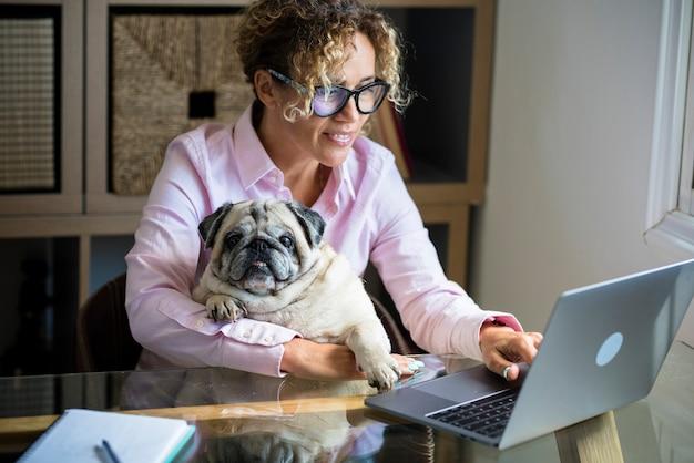 職場のデスクトップでラップトップコンピューターを使用してテクノロジーとインターネット接続を楽しんでいる幸せな無料の女性成人のための自宅でのスマートな作業現代のオンラインジョブアクティビティ