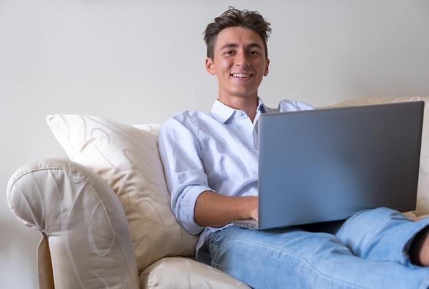 自宅のソファでノートパソコンをスマートに操作テクノロジーを駆使した若者現代のライフスタイル