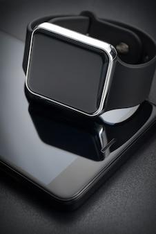 黒の背景にスマート腕時計とスマートフォン