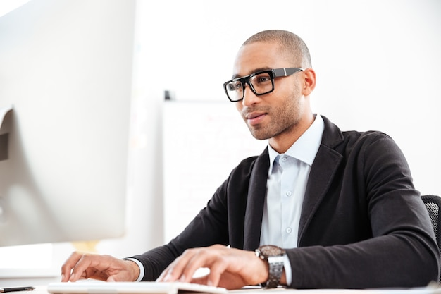 Smart young african businessman typing using computer at the office