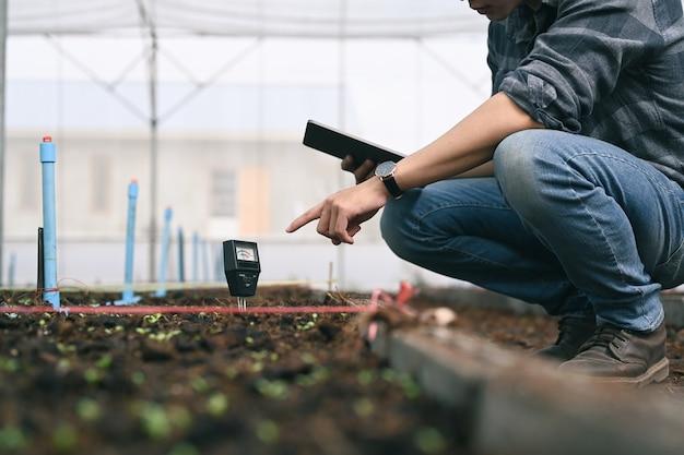 똑똑한 젊은 아시아 농학자 남자는 디지털 장치와 태블릿으로 토양을 측정합니다. 농업 기술.