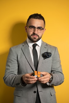 Smart young bearded handsome man in eye glasses wearing a suite holds a solved pocket cube 2x2x2 rotatable puzzle in hands while showing it on camera. isolated on yellow background.