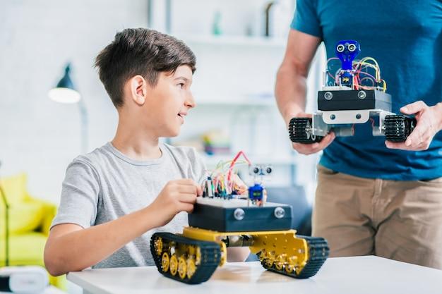 テーブルに座って彼のロボットに取り組んでいる賢い少年