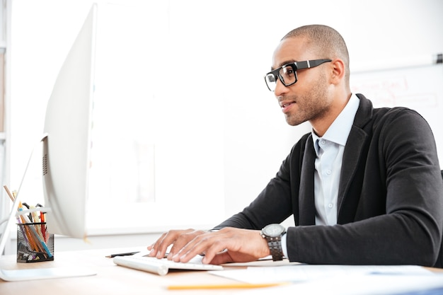 Smart young businessman looking at the computer in office