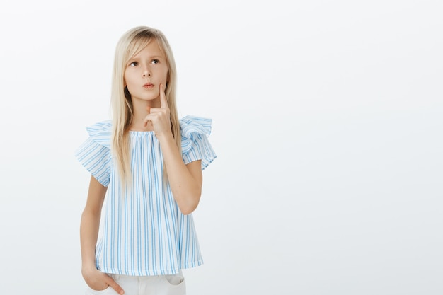 Smart young girl with blond hair, looking up and holding finger on lip, frowning while thinking, making up idea or deciding in mind, being doubtful and focused on thoughts