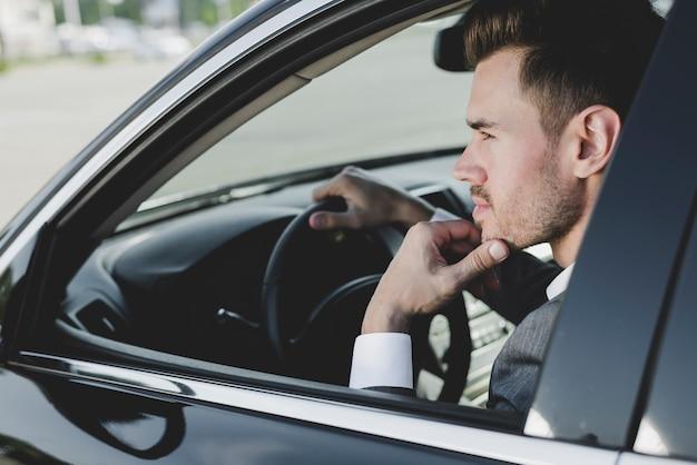 車でスマートな若いハンサムな男