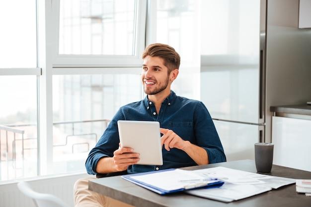 Умный молодой человек анализирует финансы с планшетом и сидит возле стола с документами, глядя в сторону