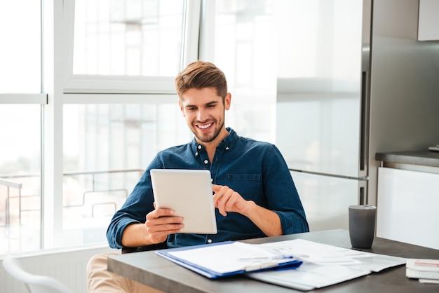 Умный молодой человек смотрит на планшет и сидит возле стола с документами
