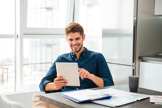 Smart young man looking at tablet and sitting near table with documents
