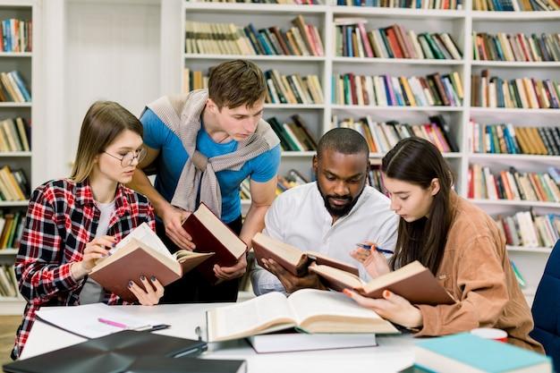 テーブルで本を読んだり、情報を探したり、大学の図書館で一緒に勉強したりするスマートな若い多民族学生