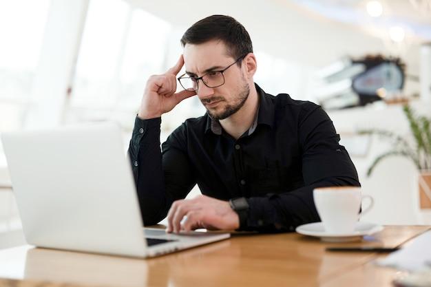 技術的なタスクについて考える賢い若い専門家。頭を抱えてノートパソコンを使用している集中男性。リモートワークのコンセプト。おいしいカプチーノのカップ。