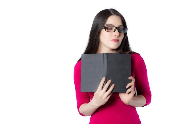 빨간 셔츠와 안경을 쓴 똑똑한 젊은 학생 여성, 그녀의 마음에 검은 책을 누르는 흰색 배경, 꿈꾸는 여성 개념 아이디어