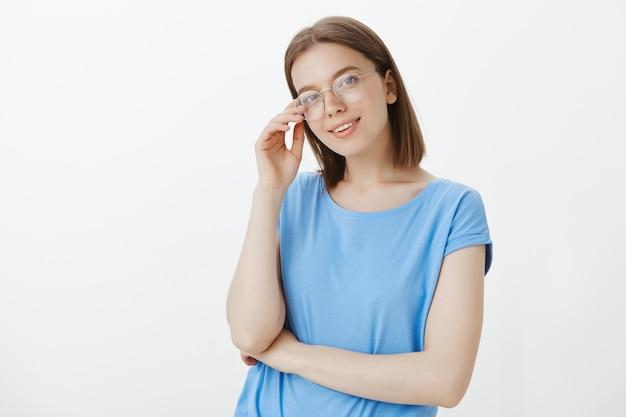 Умная молодая женщина в очках, улыбаясь довольна