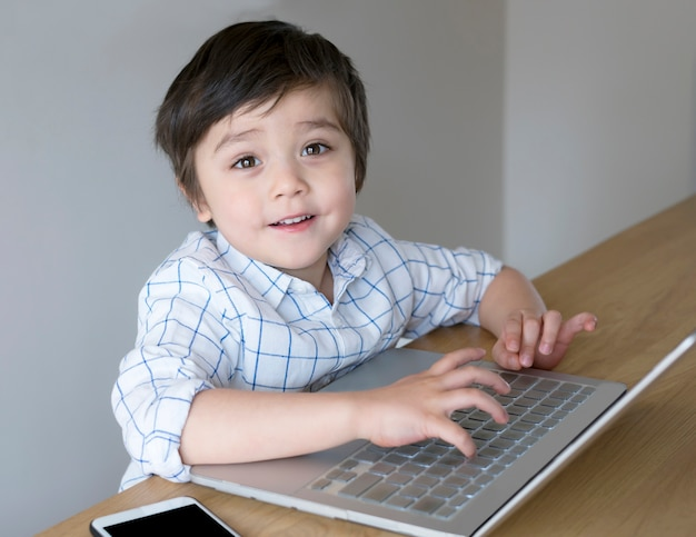 Smart мальчик, набрав ноутбук и глядя на камеру с улыбающимся лицом