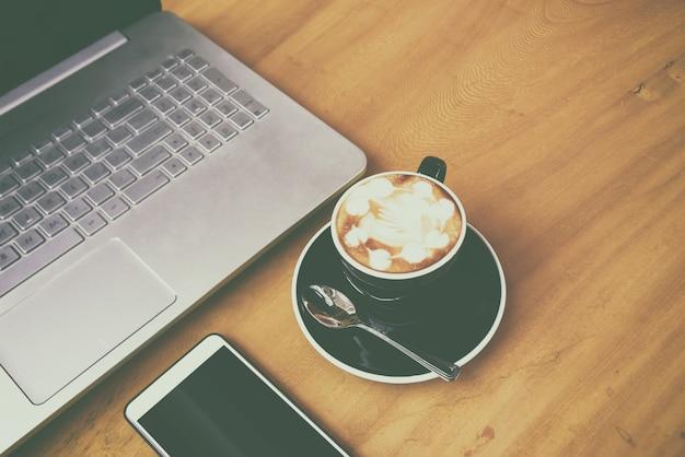 ビジネスルームの木製の机の上のsmarth電話付きのラップトップコンピューター。コーヒー休憩時間にコーヒー1杯(フィルムグレイン効果)