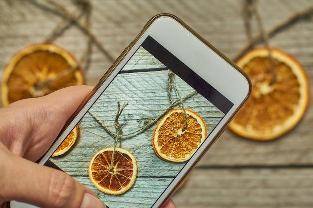 女性は、彼女の白いモダンなsmarthfoneに乾燥したオレンジのスライスで作られたクリスマスの装飾の写真を撮ります。クリスマスと新年のためにブログの同意を取る