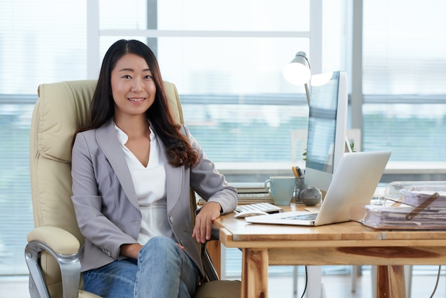 Smartly dressed asian lady sitting in office with computer and laptop and smiling