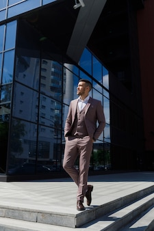 Smartly dressed businessman, modern businessman. confident young man in full suit standing outdoors with building in the background