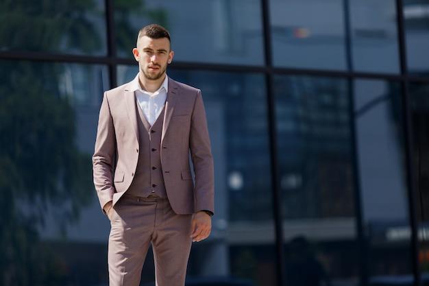 Элегантно одетый бизнесмен, современный бизнесмен. уверенный молодой человек в полном костюме, стоящий на открытом воздухе со зданием на заднем плане