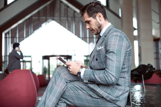 Элегантно одетый бизнесмен, улыбаясь в современном офисе