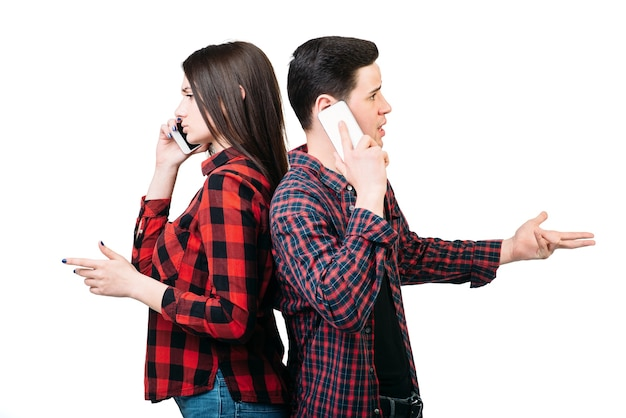 Smartphone addicted people. couple standing back to back, talking by mobile phones, white. manipulation of consciousness concept
