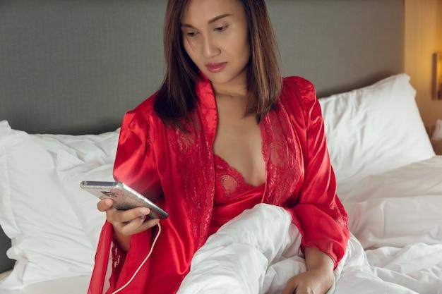 スマートフォン中毒、サテンのネグリジェと寝室に携帯電話を持った赤いローブで夜ベッドに座っているアジアの女性。眠れないので夜遅くにスマートフォンを使用して寝間着の女の子