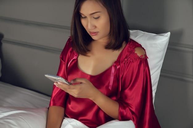スマートフォン中毒、サテンのネグリジェと赤いローブで夜ベッドに座っているアジアの女性
