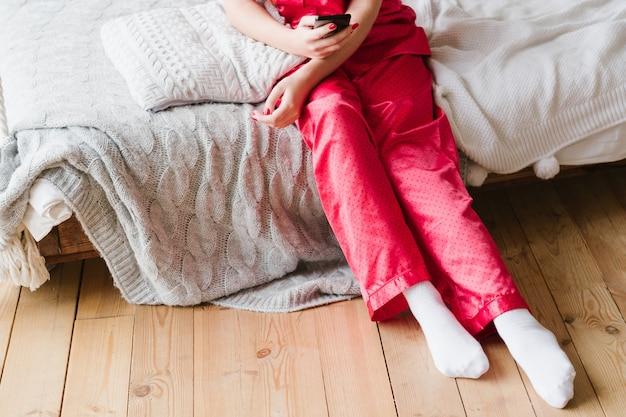 Зависимость от смартфона. женщина в пижаме, сидя на кровати со смартфоном.
