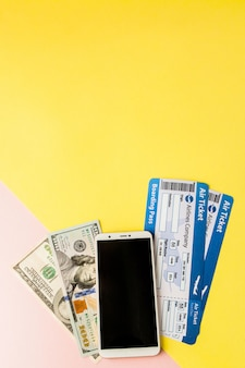 Smartphone, air ticket and dollars on pastel pink and yellow background. minimal style, flatlay.