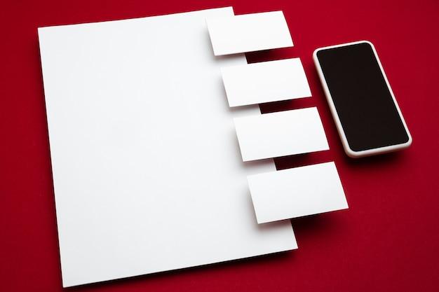 赤い背景の上に浮かぶスマートフォンと空白のチラシのポスターとカード。広告、画像、またはテキスト用のオフィススタイルのモダンなモックアップ。デザイン、ビジネス、財務のコンセプトのための空白の白いコピースペース。
