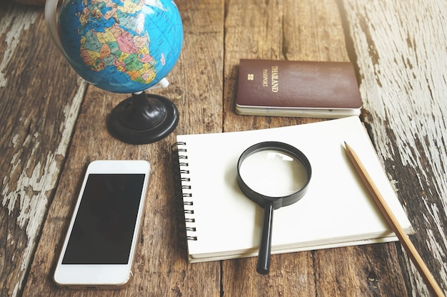 スマートフォンと木製のテーブル上の空のノート